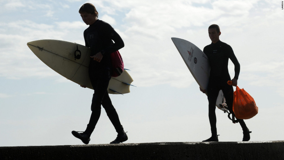 Dean Walter, left. and Henry Young walk along a seawall in Scituate, Massachusetts, with their surfboards after going into the heavy surf for about 20 minutes on Tuesday.
