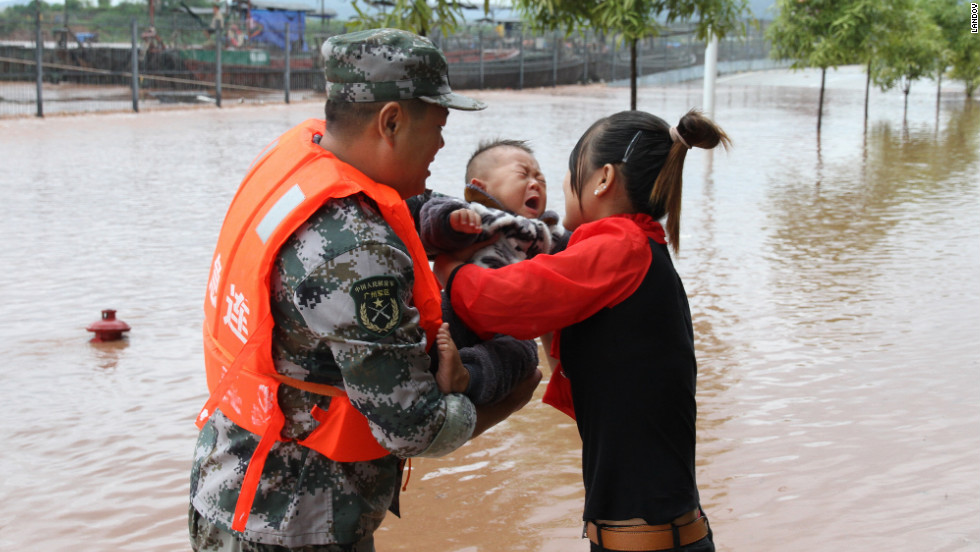 A Chinese soldier hands over a Vietnamese baby he rescued from the flood to his mother at a waterlogged market near the China-Vietnam on Monday.