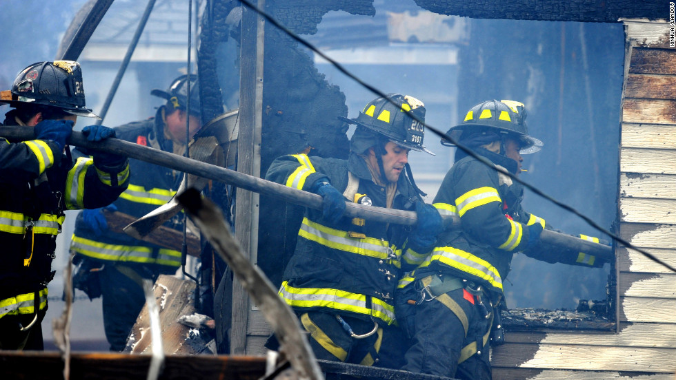 Firefighters work to extinguish flames in a home in the Breezy Point neighborhood of Queens on Tuesday. The massive fire broke out during the storm and destroyed at least 80 homes
