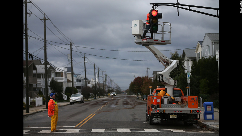Utility workers repair a traffic signal damaged by the storm in Ocean City, New Jersey, on Tuesday.