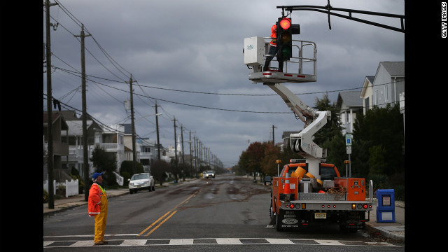 OCEAN CITY, NJ - OCTOBER 30: Utility workers repair a stop light damaged by Hurricane Sandy on October 30, 2012 in Ocean City, New Jersey. Sandy made landfall last night on the New Jersey coastline bringing heavy winds and record floodwaters. At least two dozen people were reported killed in the United States as millions of people in the eastern United States are experiencing widespread power outages, flooded homes and downed trees. (Photo by Mark Wilson/Getty Images)