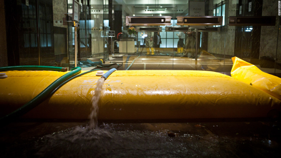 Floodwater is pumped out of a building in the financial district of New York on Monday evening.