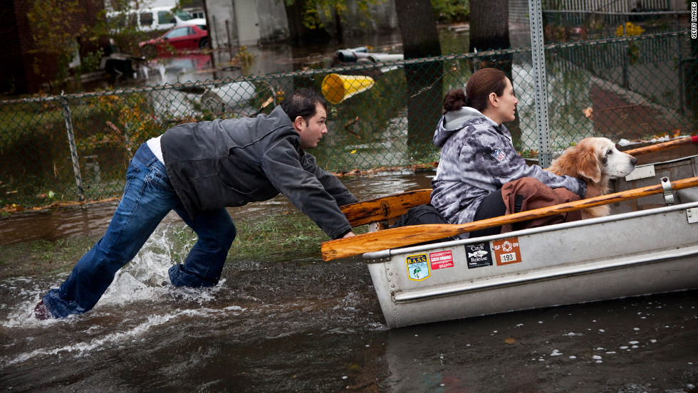 A man pushes a woman and a dog in a boat after their Little Ferry, New Jersey, neighborhood was flooded by Hurricane Sandy.