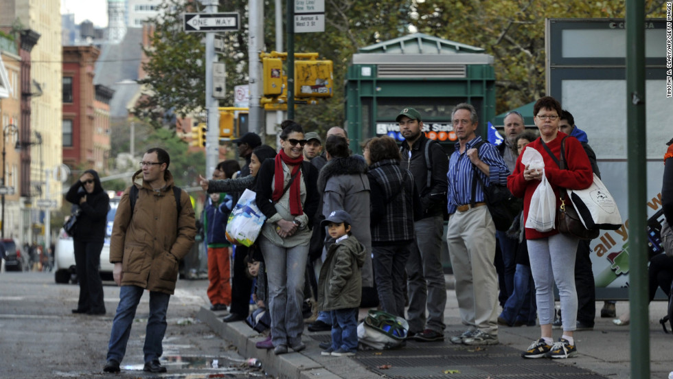 People wait for buses on Sixth Avenue in New York on Wednesday as New Yorkers cope with the aftermath of Hurricane Sandy.
