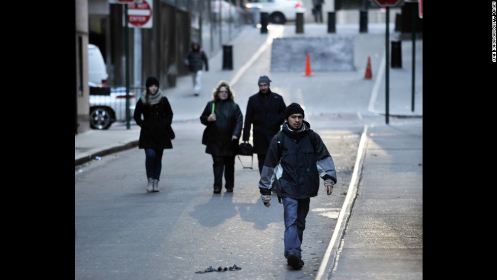 People walk to work Wednesday on a normally busy street near the New York Stock Exchange.