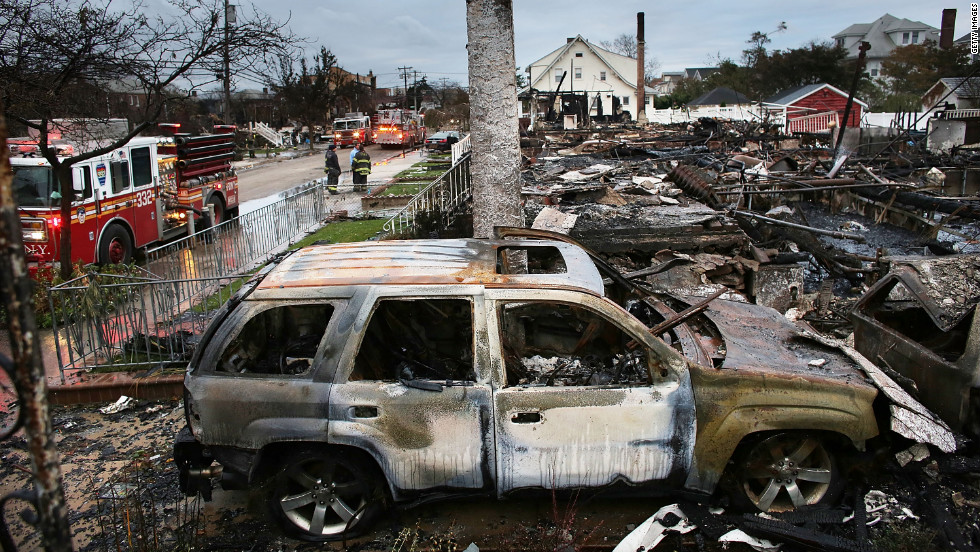 The remains of homes burned down in Rockaway are seen Wednesday, a day after an inferno spread across the flooded neighborhood.