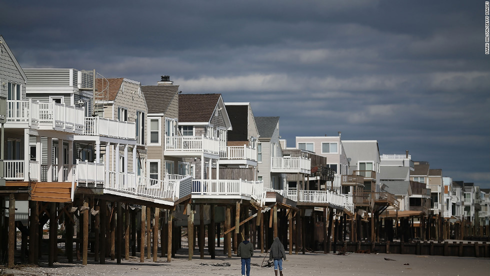 People walk past homes damaged by Hurricane Sandy  in Long Beach Island, New Jersey.