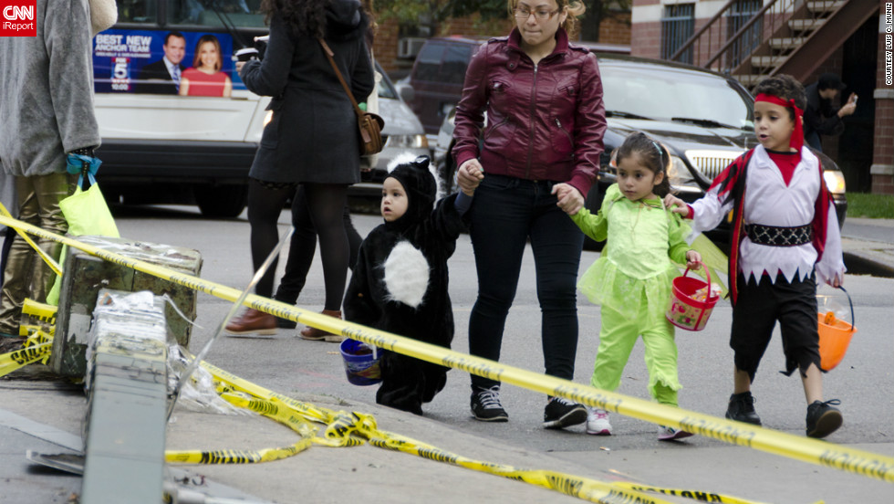 """<a href=""""http://ireport.cnn.com/docs/DOC-869953"""">Luis C. Muniz </a>photographed people in the New York borough of Brooklyn celebrating Halloween. """"Even though most of New York City is still paralyzed and without electricity, the spirit of Halloween is alive and well,"""" he said."""