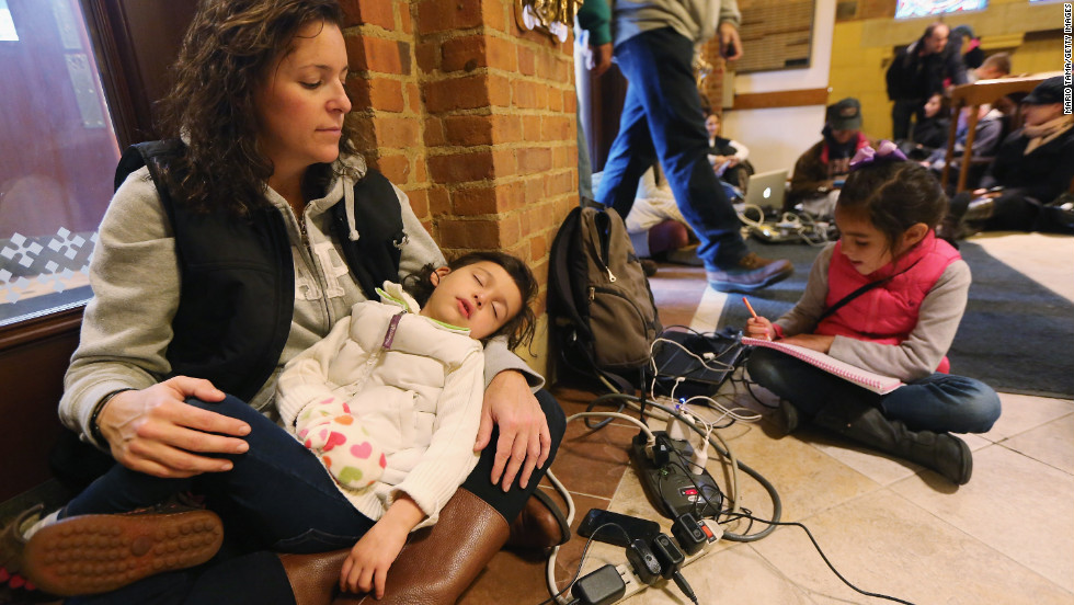 Bridget De La Torre holds her daughter Neve, 3, as daughter Paz sits nearby while they rest and charge devices on Thursday. They were at a shelter for those affected by Superstorm Sandy at Saints Peter and Paul Church in Hoboken, New Jersey. Bridget's family has no electricity or hot water, and their car was destroyed by flooding.