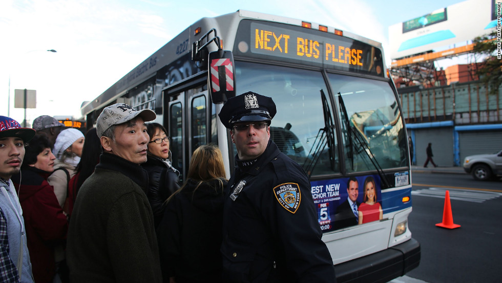 A police officer directs passengers waiting on Thursday to board city buses into Manhattan at the Barclays Center in Brooklyn. About 4,000 buses are replacing the subway lines still closed by Superstorm Sandy damage.