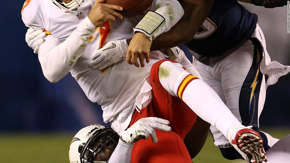 Quarterback Matt Cassel of the Chiefs is tackled by linebacker Donald Butler and cornerback Marcus Gilchrist of the Chargers.