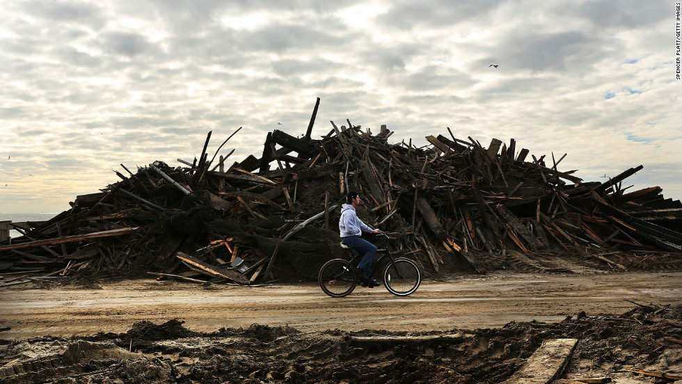 A man rides his bike through the heavily damaged Rockaway neighborhood.