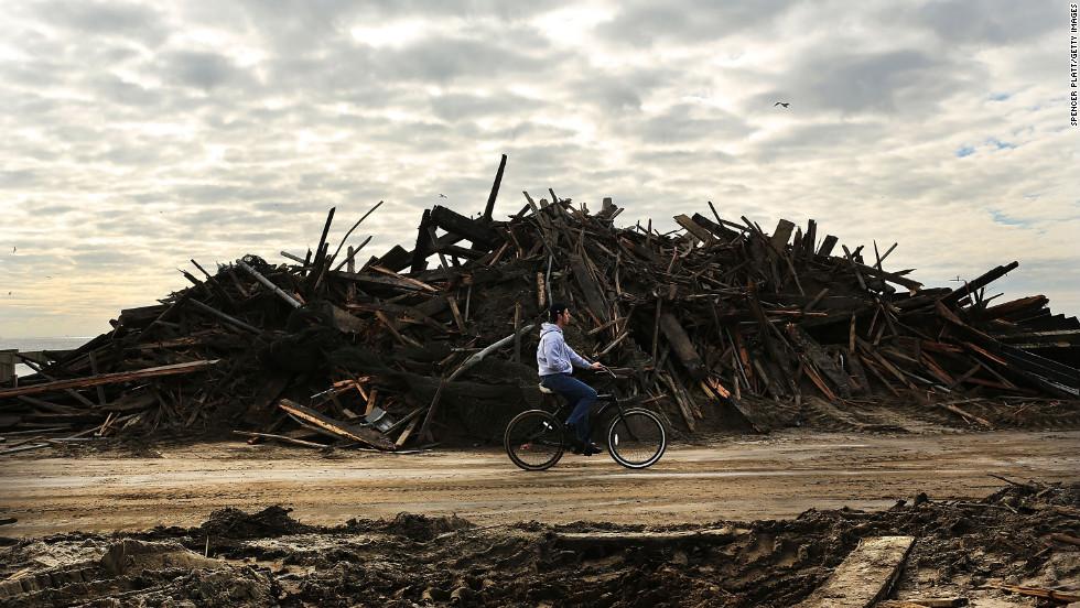 A man rides his bike through the heavily damaged Rockaway neighborhood.