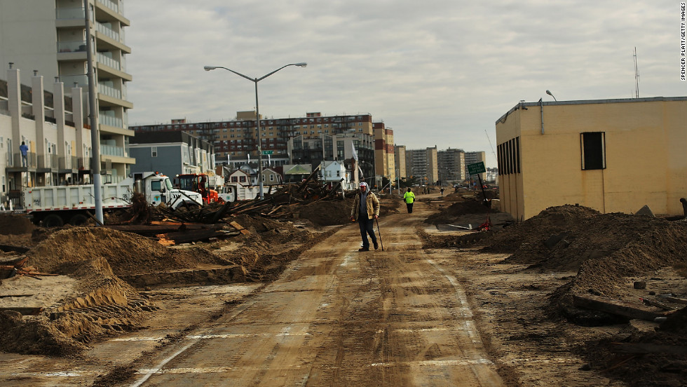 People walk through the heavily damaged Rockaway neighborhood.