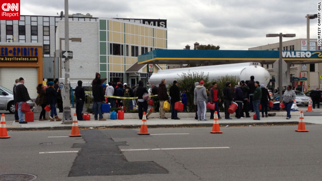People are standing in line at the only gas station operating outside of the Holland Tunnel.