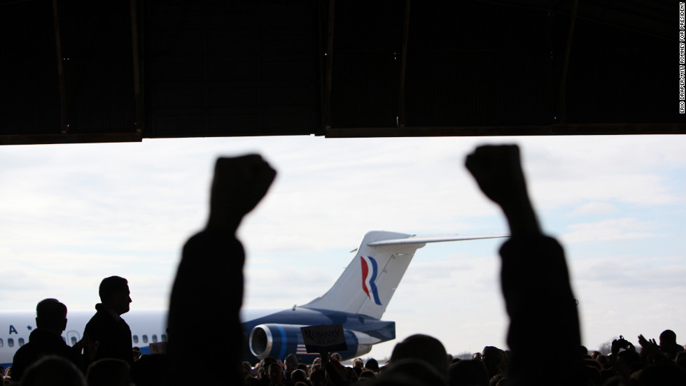 Romney is silhouetted on stage as supporters cheer during his airport rally in Dubuque, Iowa, on Nov. 2, 2012.