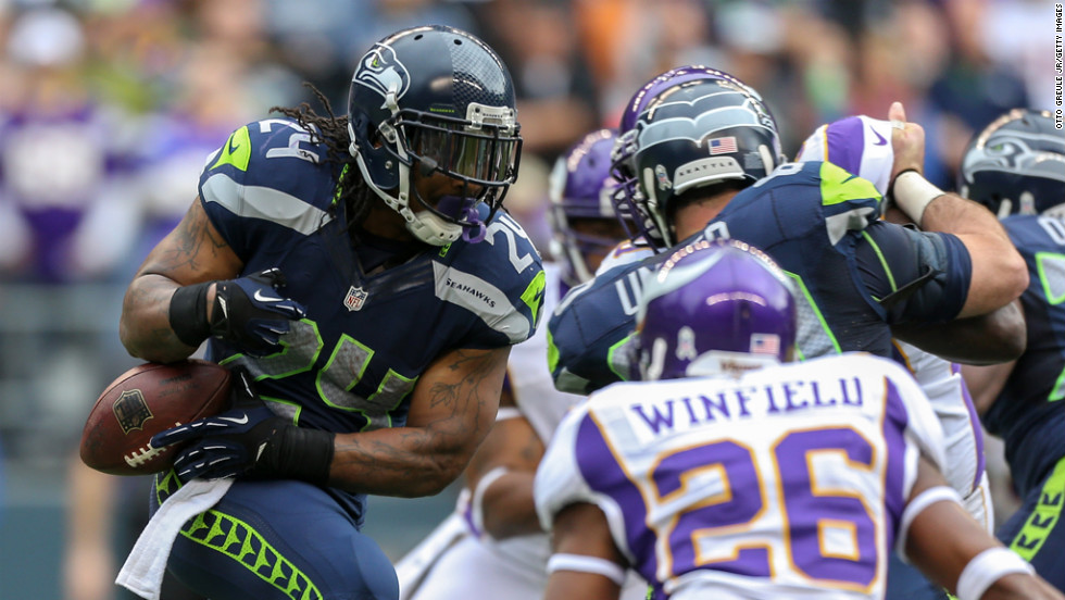 Running back Marshawn Lynch of the Seahawks rushes against cornerback Antoine Winfield of the Vikings on Sunday.