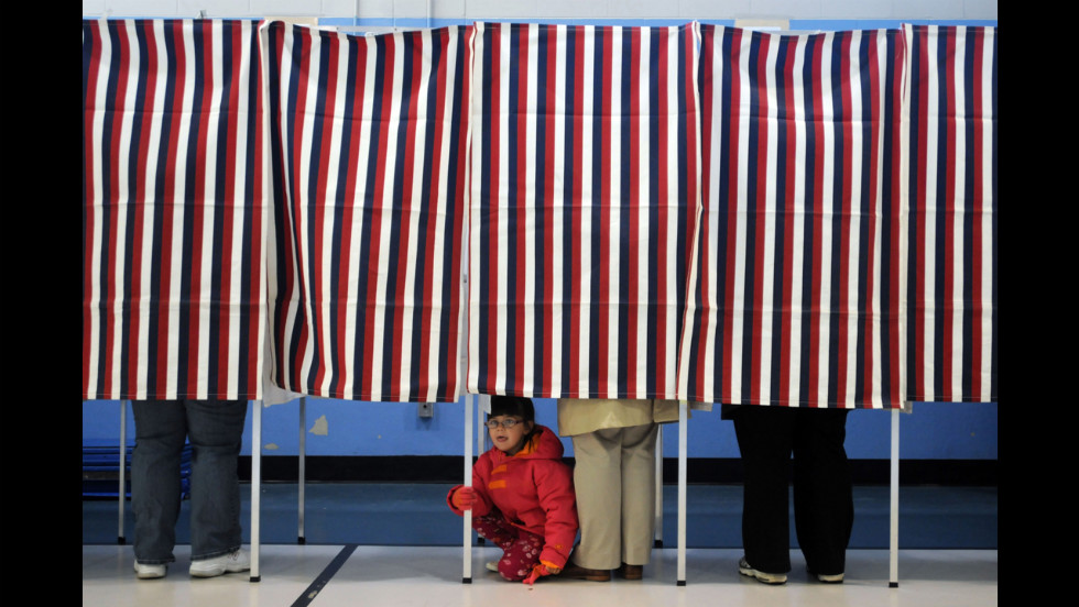 A young girl peered out from under a voting booth as her mother cast a ballot at the Bishop Leo O'Neil Youth Center in Manchester, New Hampshire.