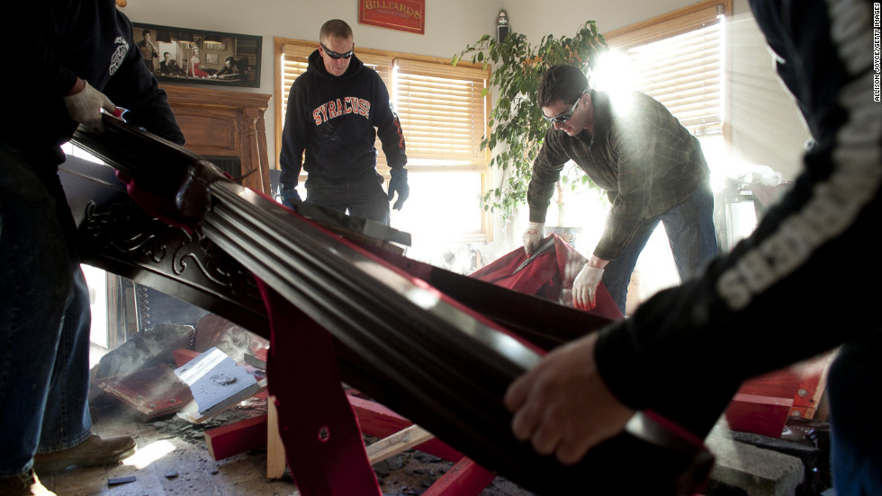 Volunteers who call themselves the Broad Channel Police Department help clean a neighbor's damaged house.
