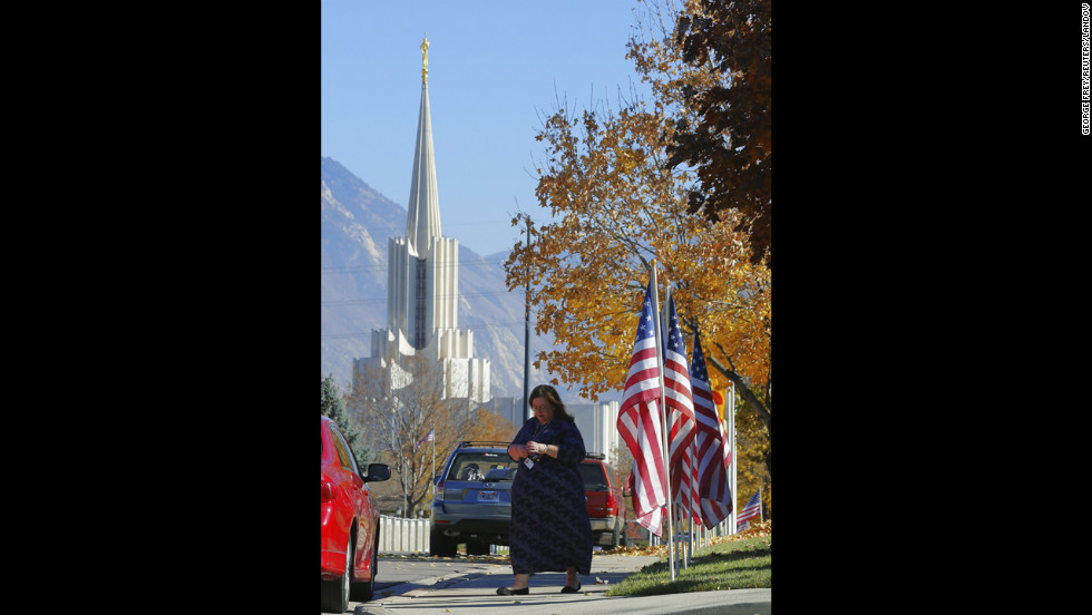 A woman walks out of a polling place after voting in South Jordan, Utah. The Jordan River Utah Temple of the Church of Jesus Christ of Latter-day Saints is visible in the background.