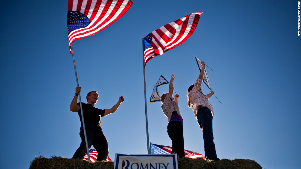 Justin Stucki, Leah Quirk, and Kenady Pettingill, left to right, urged drivers to vote for Republican presidential candidate Mitt Romney in Spanish Springs, Nevada.