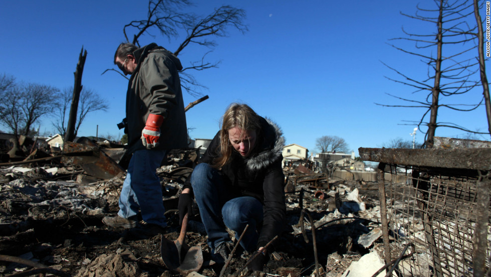 People sift through their damaged home on Sunday in Breezy Point.