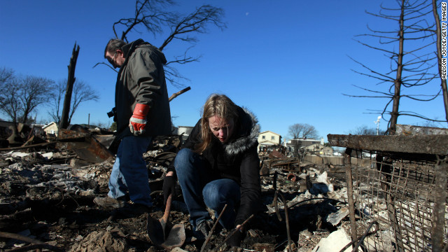 People sift through their damaged home for items to save in the Breezy Point neighborhood of Queens, New York.