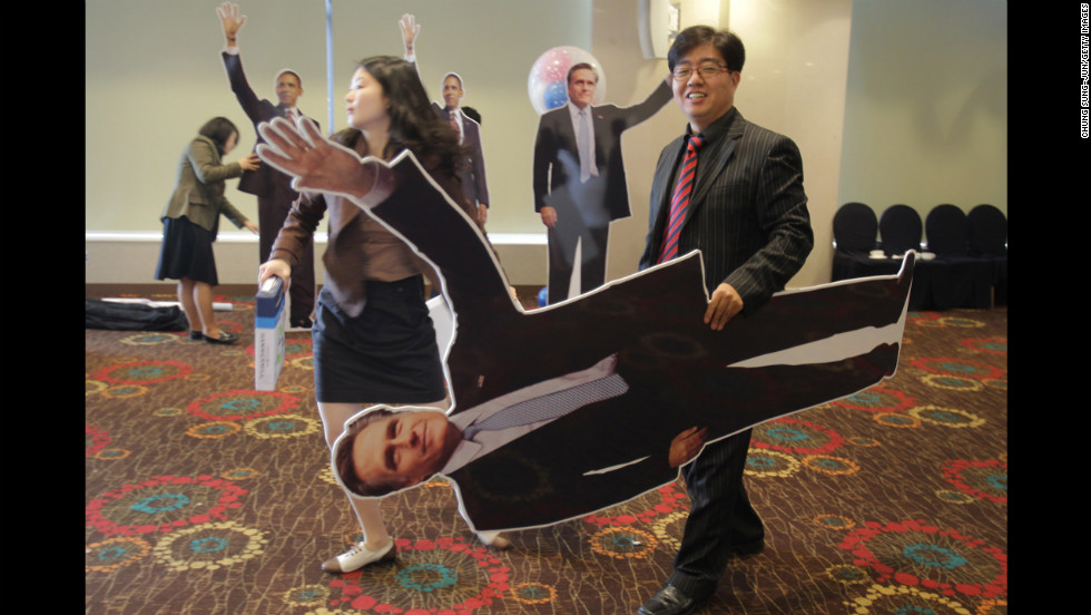 A South Korean man carries a cutout picture of Republican presidential candidate Mitt Romney after an election screening Wednesday in Seoul.