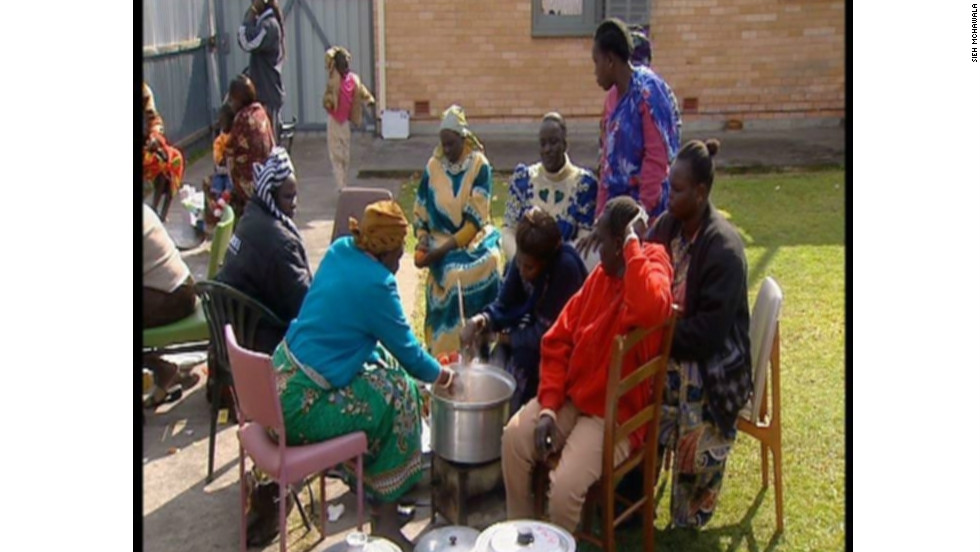 Cooking is women's work in the Dinka culture of South Sudan. These women are cooking in the backyard of a house in Adelaide, Australia.