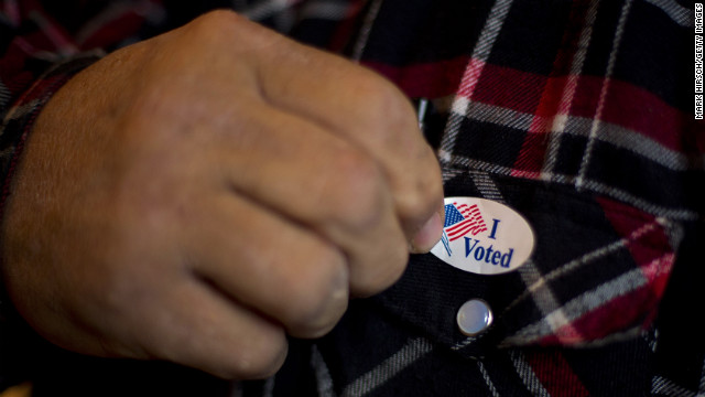 """OTTER CREEK, IA- NOVEMBER 6:   A man puts on his """"I Voted"""" sticker after voting at a polling station on November 6, 2012 in Otter Creek, Iowa. U.S. citizens go to the polls today to vote in the election between Democratic President Barack Obama and Republican nominee former Massachusetts Gov. Mitt Romney.  (Photo by Mark Hirsch/Getty Images)"""