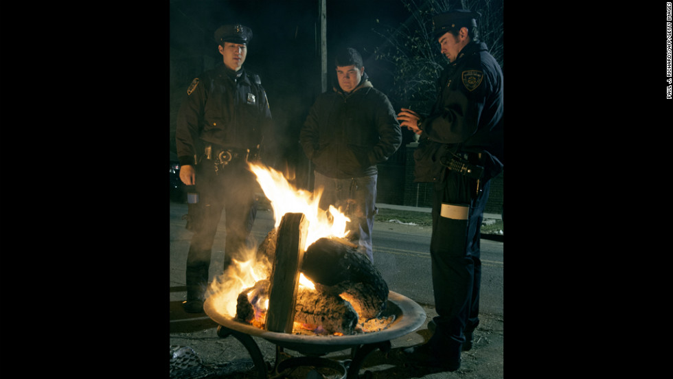 New York City police officers and a resident warm up in front of a fire in a blacked-out area of Oakwood Beach on Staten Island.