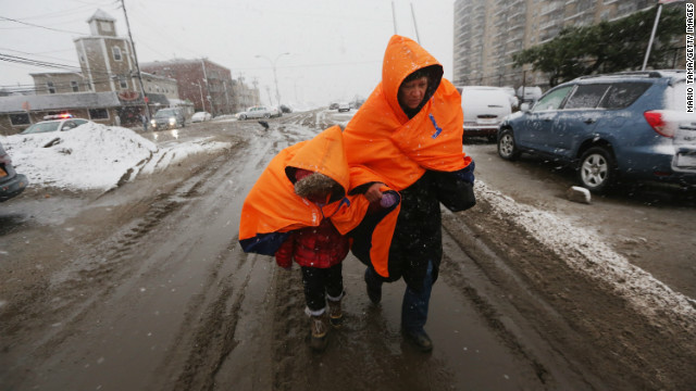 NEW YORK, NY - NOVEMBER 07:  Fatima Quentiro walks with her granddaughter Galalea Castro through the snow to a bus stop to take a bus to Quenitro?s home after Castro?s home was damaged by flooding as a Nor?Easter approaches in the Rockaway neighborhood on November 7, 2012 in the Queens borough of New York City. The two are wearing jackets donated by the NYC Marathon. The Rockaway Peninsula was especially hard hit by Superstorm Sandy and some are evacuating ahead of the coming storm.  (Photo by Mario Tama/Getty Images)