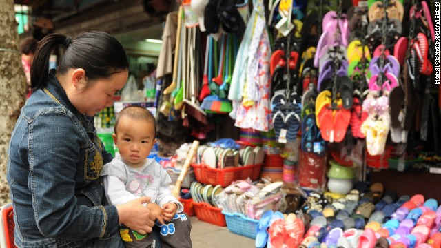 A mother sits with her child outside a shop on a street in Shanghai on May 23, 2012. China's economic growth will continue to ease this year, presenting policy makers in Beijing with the challenge of preventing an excessively abrupt slowdown, the World Bank said in a report.