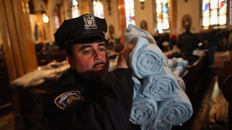 A police officer carries blankets donated by Ikea for people affected by Superstorm Sandy in Brooklyn.