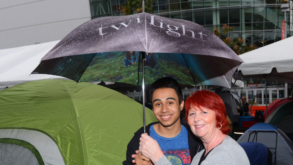 "Two fans brave the rain with a ""Twilight"" umbrella at tent city."