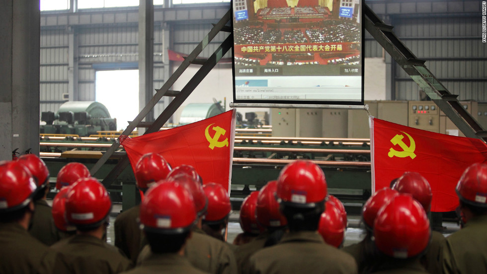Workers gather to watch Hu's address to the Communist Party Congress. Hu called for stepped-up political reform and a revamped economic model on the first day of the congress.