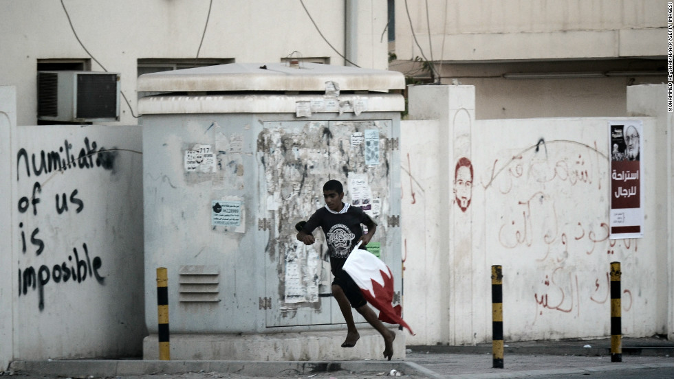 A Bahraini Shiite protester runs for cover from riot police after a crackdown on an anti-government demonstrator. They were protestsing against the killing of 16-year old Ali Abbas Radhi in the village of Diraz, west Manama on  November 9, 2012.