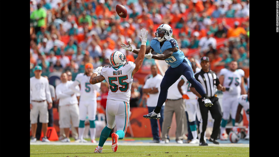 Darius Reynaud of the Tennessee Titans goes up for a catch over Koa Misi of the Miami Dolphins during a game at Sun Life Stadium on Sunday in Miami Gardens, Florida.