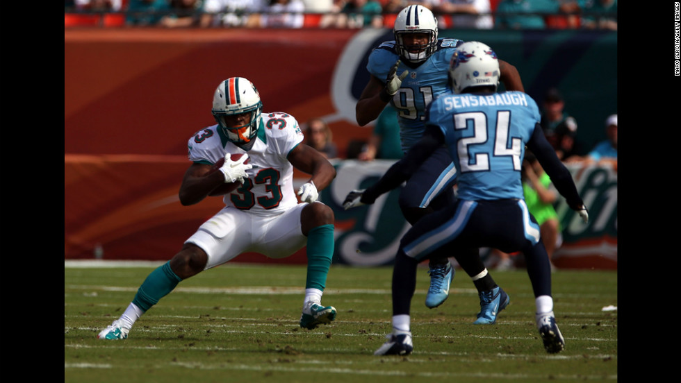 Running back Daniel Thomas of the Dolphins runs against Coty Sensabaugh of the Titans on Sunday.