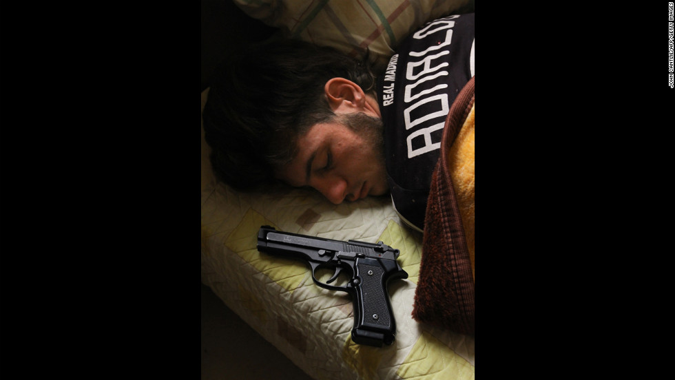 Syrian opposition fighter Bazel Araj, 19, sleeps next to his gun in Aleppo on Sunday, November 11.