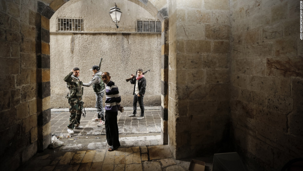 Syrian opposition fighters pass a civilian as they patrol the northern city of Aleppo on Sunday.