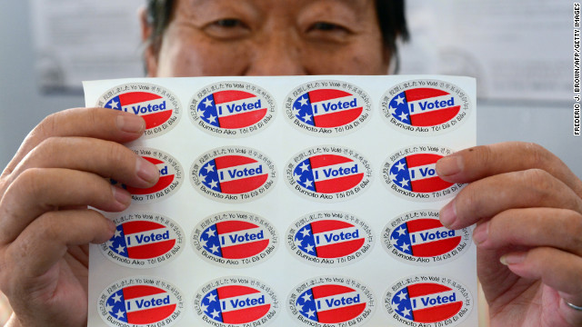 "Election official Henry Tung displays a sheet of ""I Voted"" stickers in several languages at a Los Angeles-area polling station."