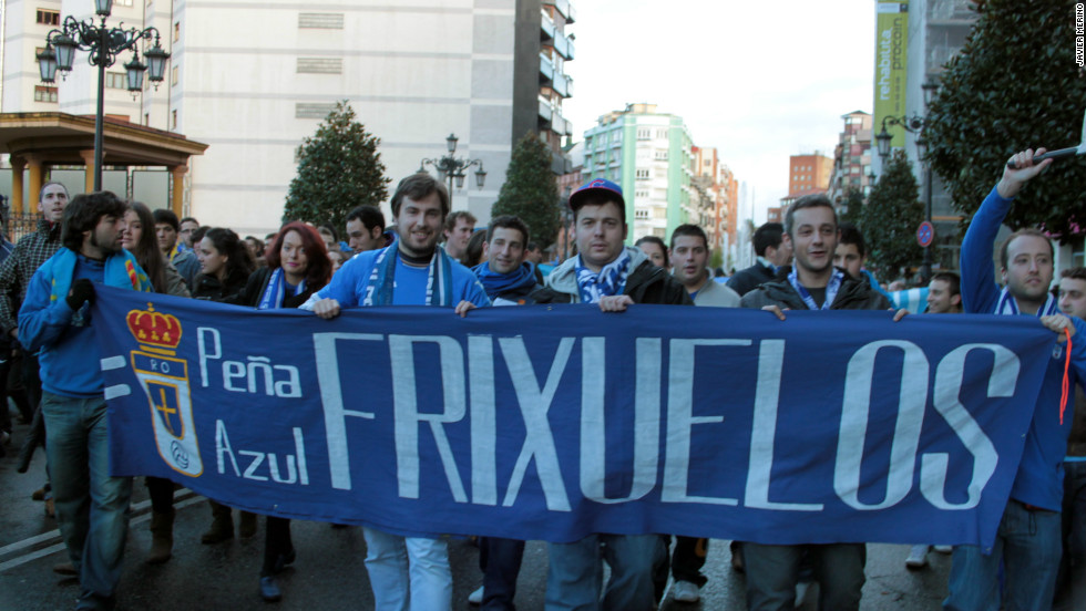Real Oviedo fans hold up banner as they march through the city on their way to the league match to protest against the possible closure of the club due to financial difficulties.