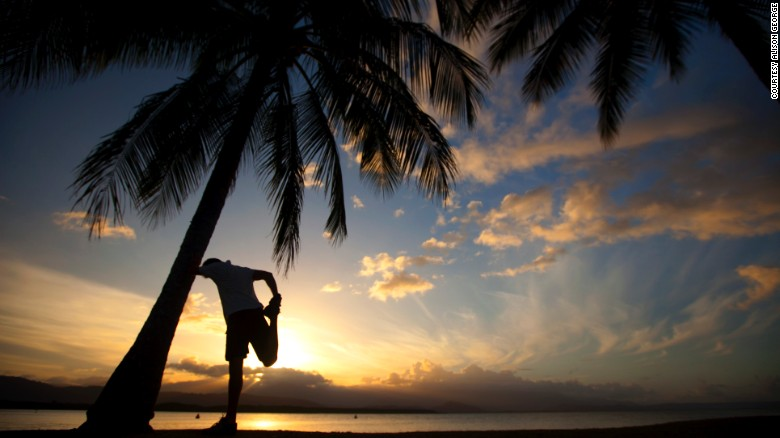 A runner stretches his legs whilst leaning against a palm tree in Queensland, Australia.