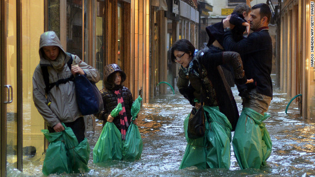 Parents carry their children in a small street during a 'acqua alta' on November 11, 2012 in Venice.