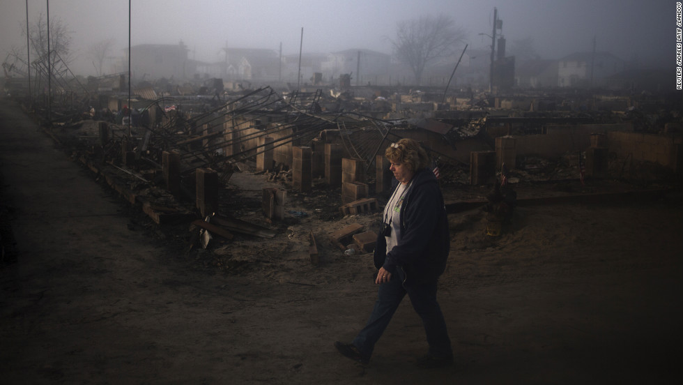 A resident of Breezy Point in Queens walks past houses destroyed by fire during Sandy on Monday.
