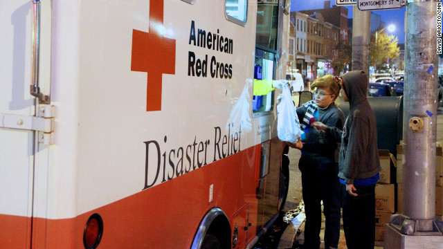 Red Cross personnel distribute food and supplies to storm-affected residents in Jersey City.