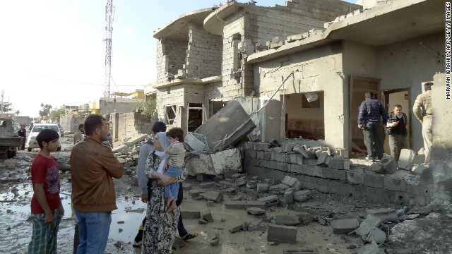 An Iraqi family looks at the damage to a building following one of two car bombs in the northern Iraqi city of Kirkuk, on November 14, 2012.