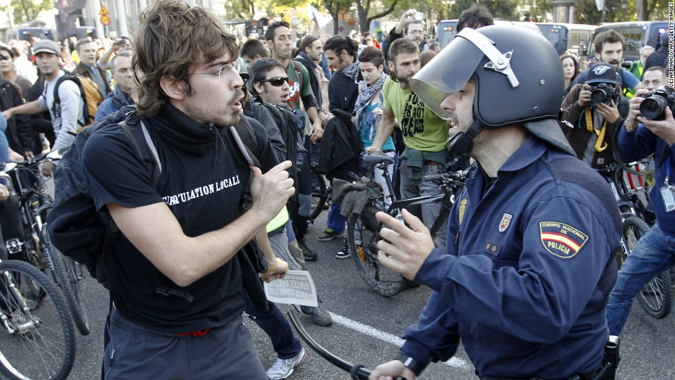 A protester clashes with a riot policeman at Cibeles Square in Madrid.