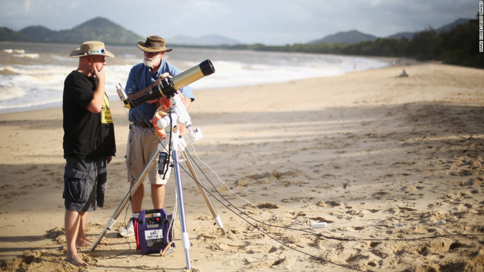 Jonathan Bradshaw and Terry Cuttle set up telescopic cameras and computer equipment on Palm Cove beach in preparation to run a live stream via NASA of the total solar eclipse in Cairns on Tuesday.